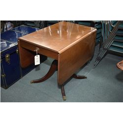 Mid 20th century walnut drop leaf center pedestal table with single drawer and brass capped claw fee