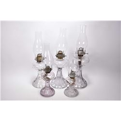 Set of five matching and graduated sized colourless press glass oil lamps including one turning purp