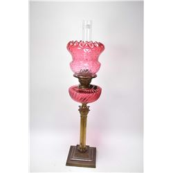 Antique cranberry glass British made oil lamp on Corinthian column base
