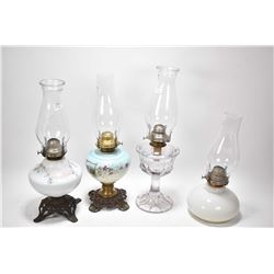 Four vintage oil lamps including colourless glass, cast and glass etc.