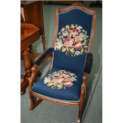 Antique open arm rocking chair with carved grape and leaf decoration and needlepoint upholstered sea
