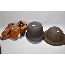 Leather munitions belt, a Canadian military helmet and a German military helmet