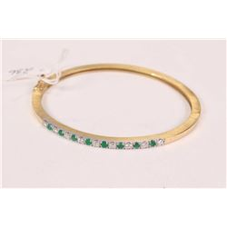 14kt yellow and white gold emerald gemstone and diamond hinged bracelet. Set with .36cts of full rou