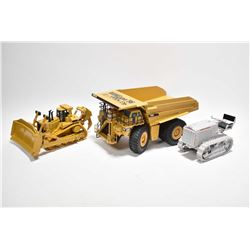 Three die cast heavy equipment vehicles including a Caterpillar 793C 1:50th scale dump truck made by