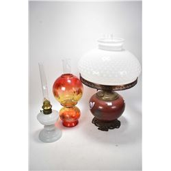 Three vintage oil lamps including one banquet lamp with milk glass shade and handpainted font etc.