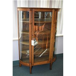 Quarter cut oak Canadiana curved glass china cabinet with single door and paw feet