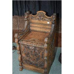 "Antique English oak coal hod/ monk's chair with carved faces and florals, labelled ""Hewetson Milner"