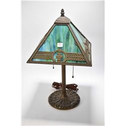 Antique Arts & Crafts table lamp with four green slag glass panel shade and cast base marked Miller