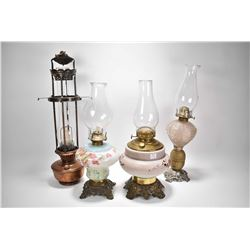 Four vintage oil lamps, three with cast bases and glass fonts plus a copper Aladdin lamp with shade