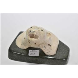 Inuit carving on what appears to be whale bone vertebra of polar bear bust on a green soapstone base