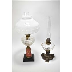 Two antique oil lamps each with cast bases and glass fonts