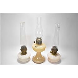 Three oil lamps including two matching Aladdins and a Coleman