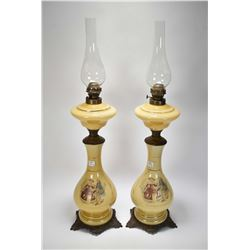 Pair of matching tall glass and cast oil lamps with transferware love story scenes