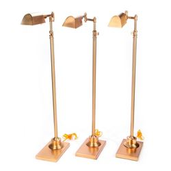Three brass floor lamps.