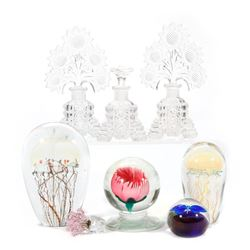A collection of glass paper weights and perfumes.