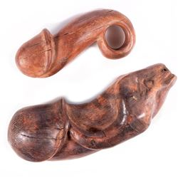 Two carved wooden phalluses.