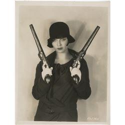 Louise Brooks exceptional portrait photograph with flintlock pistols.