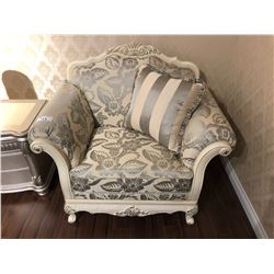 OVER SIZED LOUNGE CHAIR WITH FLORAL PRINT AND WOOD TRIM.