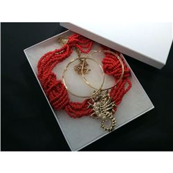 Red fabric designer necklace with golden seahorse motif.
