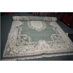 """Sculpted wool area carpet in shades of sage green cream and pale pastels, fringed edges, 102"""" X 152"""""""