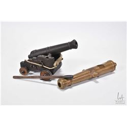 "Two miniature cannons including 8"" brass cannon sans cart and a 6"" cannon on a wooden cart with a ta"