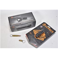 New in box Streamlight Stroin flashlight with charger, a Gerber multi tool, new in package and two b