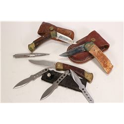 Three pocket knives, two with leather pouches, a set of three throwing knives and a metal spike.