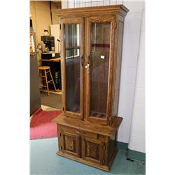 Large oak and glass locking four door gun display with lowered storage and two glazed door, set up f