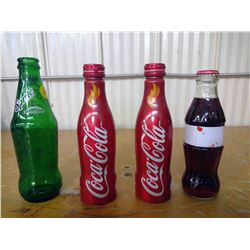 three coca cola bottles (unopened)and one empty sprite bottle