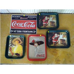 four coca cola trays and one coca cola tin sign