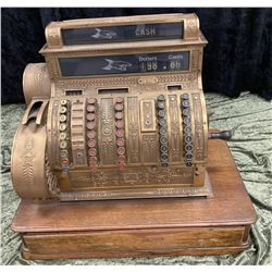 "Fancy Brass cash register. $99.99 highest  denomination. Measures 22 1/2"" by 25"" wide by  16"" deep."