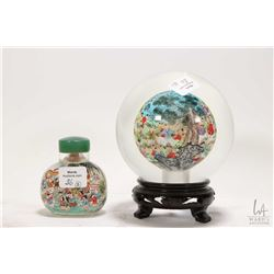 "Two pieces of Chinese reverse painted glass including 5"" glass ball on wooden plinth and a 2 3/4"" sn"