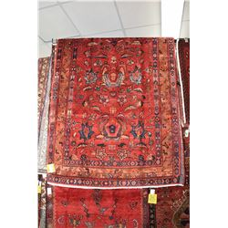 100% handmade Irak wool area carpet with overall floral design, red background and highlights of nav