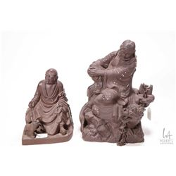 "Two Oriental fired clay figures including 9"" figure with dragon guardian and 6 1/2"" Buddha type"