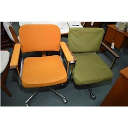 Two mid century open arm swivel office chairs, one with green upholstery and one in orange