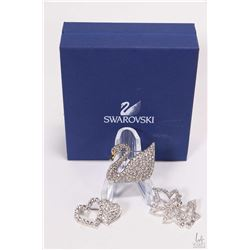 Three Swarovski crystal brooches including swan, three leaf brooch and a double heart brooch