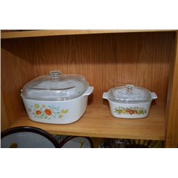 Shelf lot of oven to table ware including two large lidded casserole dishes, a small lidded casserol