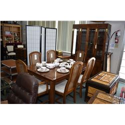 Eight piece oak dining suite including large table with two skirted insert leaves, six rattan dining