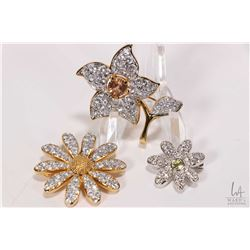 Three signed Swarovski crystal brooches including two gold tone flowers and silver tone daisy