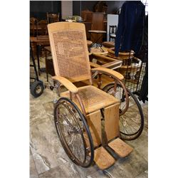 Antique wheelchair with woven rattan seat and back