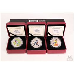 Three Royal Canadian Mint cased collector coloured coins including 2012 Rose-breasted Grosbeak 25 ce