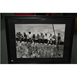 Framed black and white photographic print of ironworkers on their lunch break