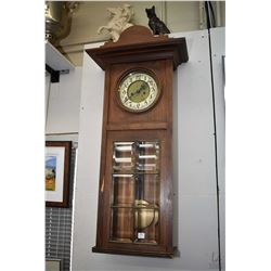 Antique wall hanging wood cased clock with visible pendulum behind six bevelled glass panels, not wo