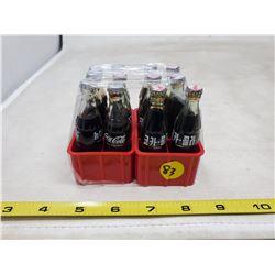 (2) Coca Cola miniatures 6 full bottles each (foreign language)