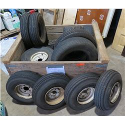 Wood Box full of new and used trailer tires with some rims.