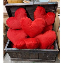 Weathered wooden chest with stuffed heart cushions