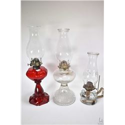 Three vintage oil lamps including ruby glass heart motif lamp with clear hurricane, a colourless lam