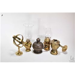 Three brass oil lamps, a brass oil lamp font and two wall brackets