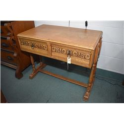 Antique two drawer oak console table with decorative scroll panels and turned supports