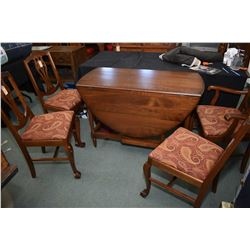 Mid 20th century walnut drop leaf, gate leg table with four side chairs featuring upholstered seats